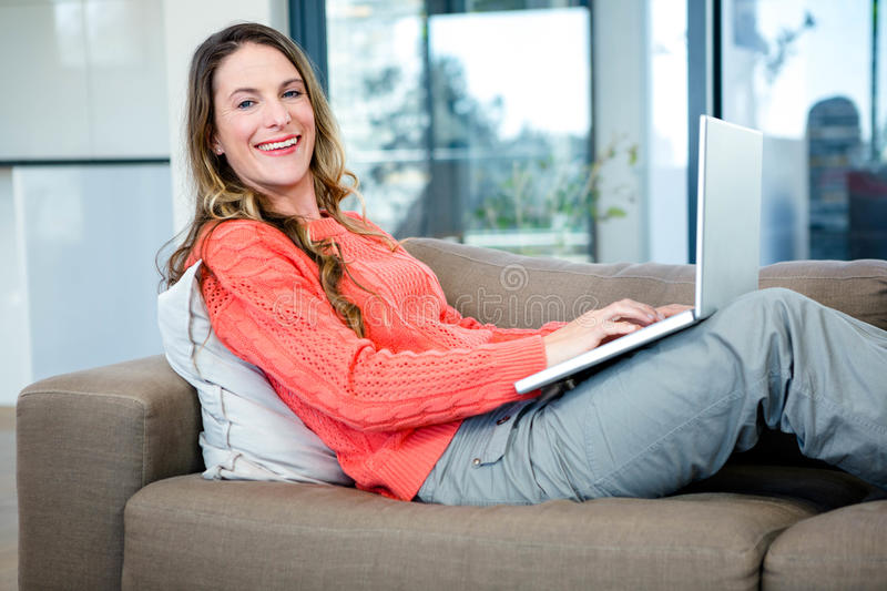 Smiling woman typing on her laptop. Smiling woman lying on the couch typing on her laptop stock photos
