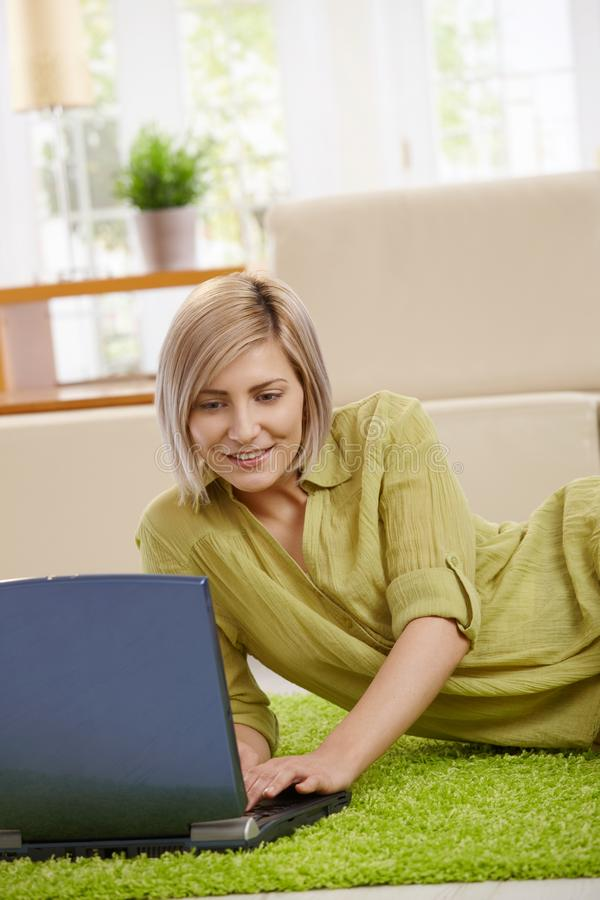 Woman with laptop. Smiling woman typing on laptop keyboard, lying on floor at home stock photography