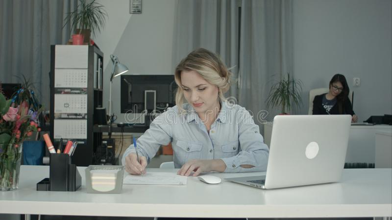 Smiling woman typing on laptop and taking notes at her office desk stock photography