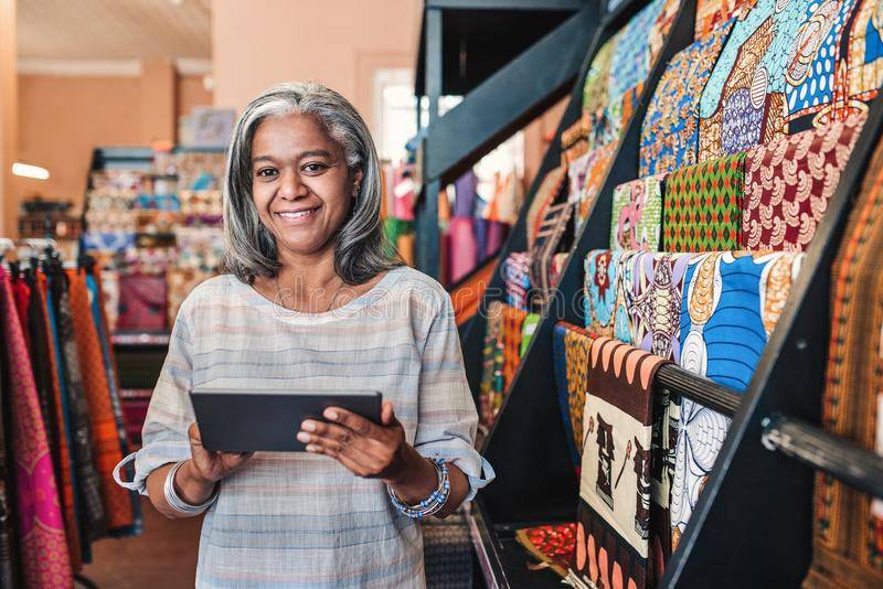 Smiling woman using a digital tablet in her textiles shop. Portrait of a smiling mature fabric shop owner standing next to racks of colorful cloths and textiles stock photos