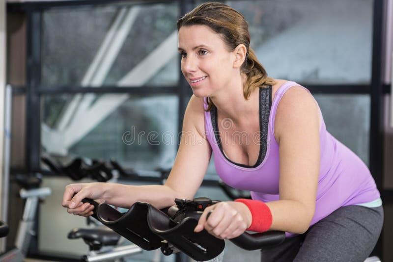 Smiling woman using exercise bike stock photos