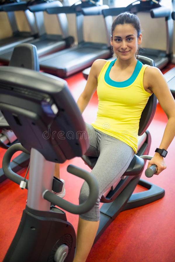 Smiling woman using exercise machine stock image
