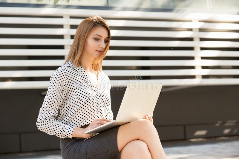 Smiling woman using her laptop outside royalty free stock photo