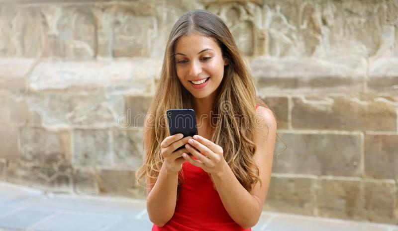 Smiling woman using mobile phone app to play video games online. City woman relaxing. Urban lifestyle. Banner crop for advertising royalty free stock image