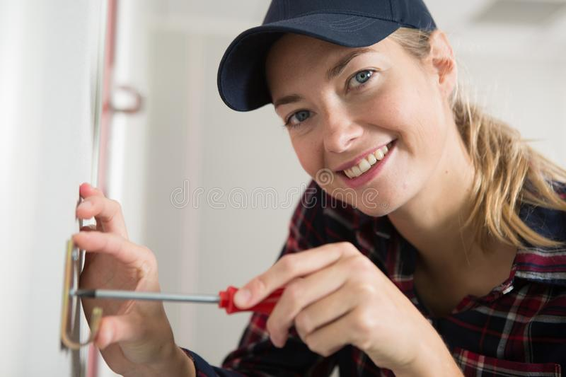 Smiling woman using screw on wall. Smiling woman using a screw on a wall stock photos