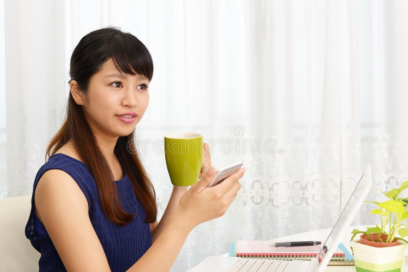 Smiling woman using a smart phone. Woman who enjoys the coffee break stock image
