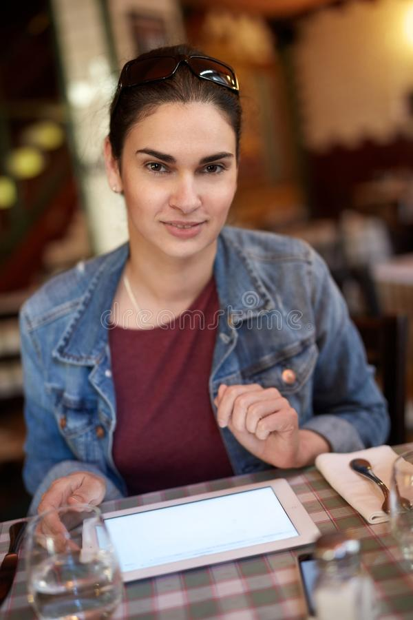Smiling woman using tablet in restaurant. Portrait of smiling woman using tablet in restaurant. Tablet screen is blank waiting for your logo royalty free stock photos