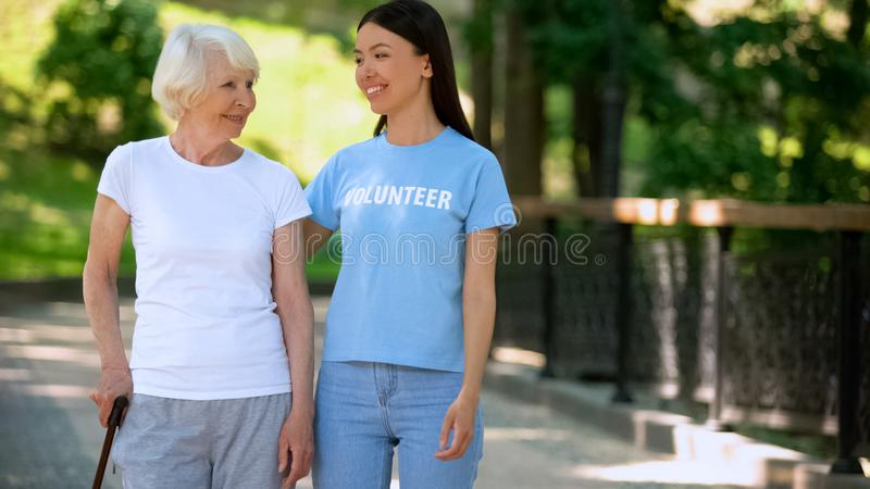 Smiling woman volunteer t-shirt and happy aged lady walking nursing home garden. Stock photo stock photo