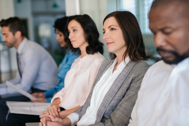 Smiling woman waiting with other job applicants in an office royalty free stock image
