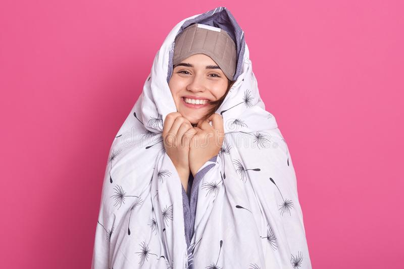 Smiling woman wakes up in morning, posing with blanket and blindfold eyes mask for sleep, having happy facial expression, has royalty free stock photography