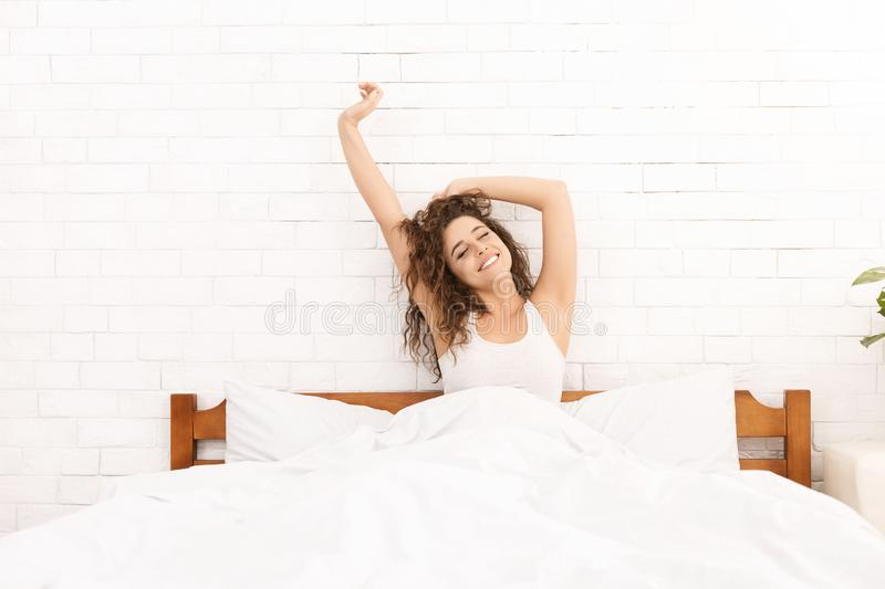 Smiling woman waking up in her bed royalty free stock image