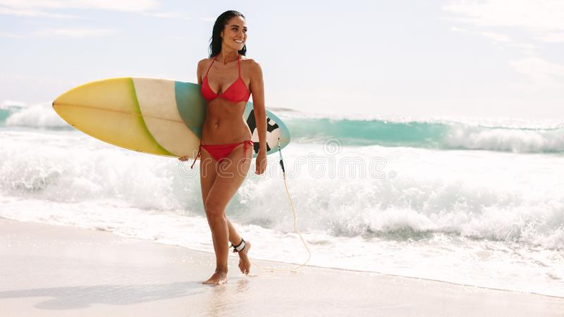 Smiling woman walking out of sea with surfboard stock photo