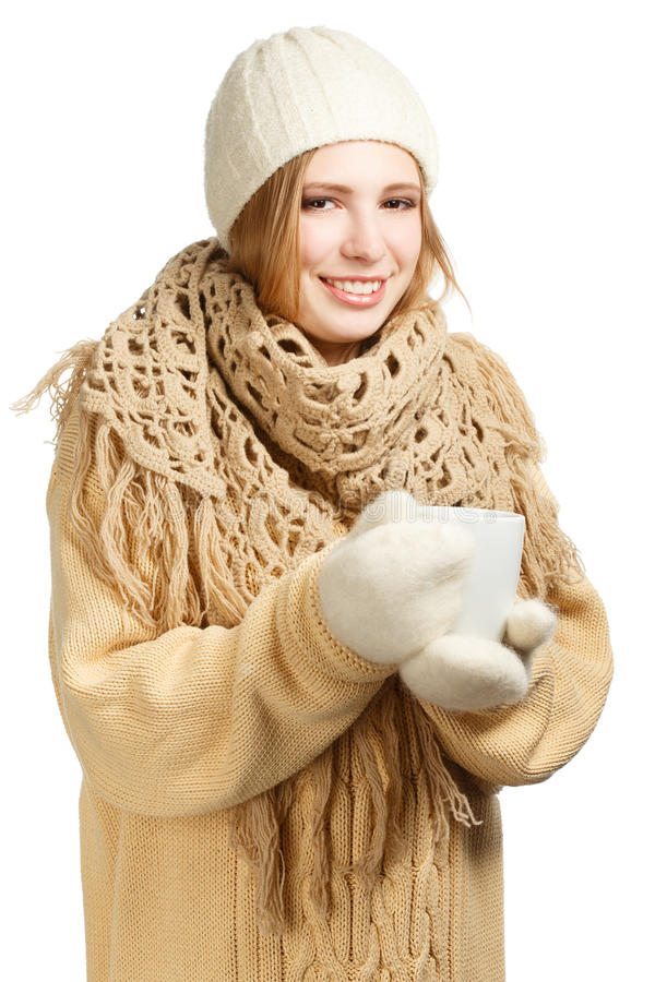 Smiling woman in warm clothing with mug. Young smiling woman in warm winter clothing with mug isolated on white background stock photo
