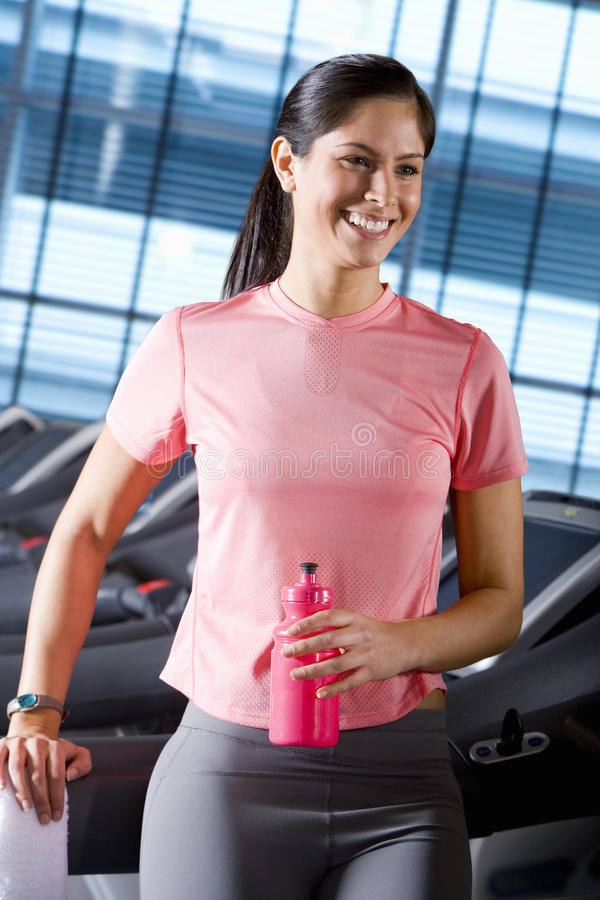 Smiling woman with water bottle leaning on treadmill in health club stock photography