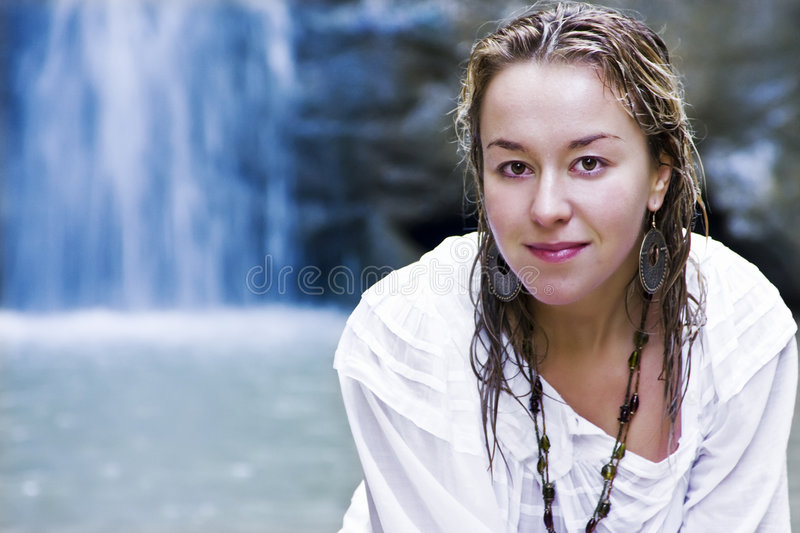 Smiling woman in waterfall royalty free stock image