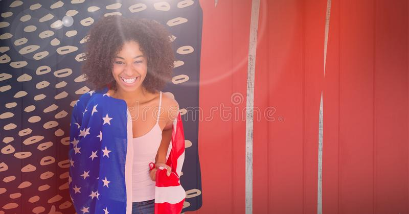 Smiling woman wearing an american flag on her shoulders. Digital composite of Smiling woman wearing an american flag on her shoulders royalty free stock images