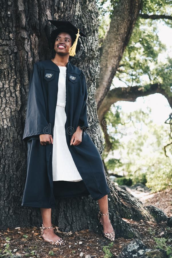 Smiling Woman Wearing Black Academic Gown and Hat Leaning Behind Tree royalty free stock images