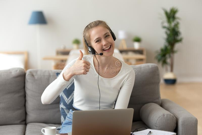 Smiling woman wearing headset showing thumbs up looking at camera. Happy girl student like distance education, recommend training or work on laptop, e-learning royalty free stock photos