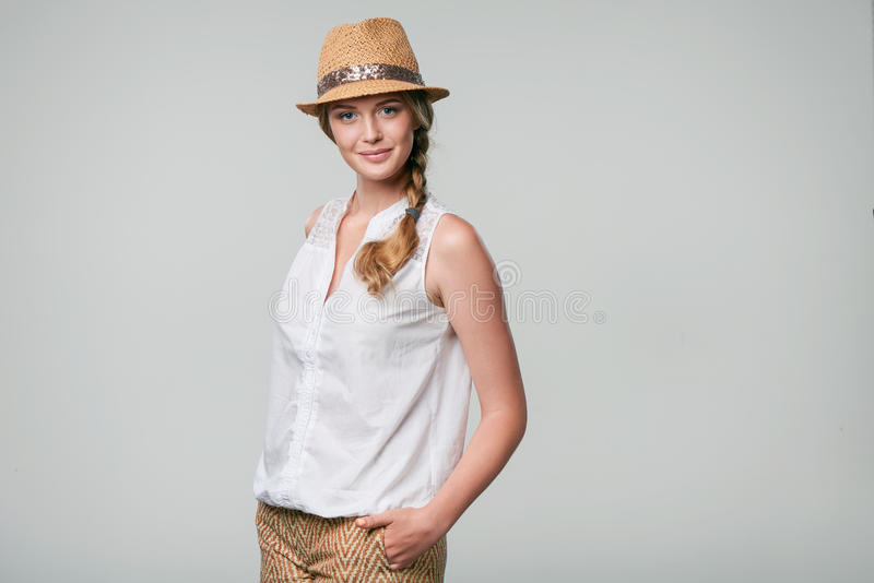 Smiling woman wearing summer straw fedora hat. Beautiful smiling woman wearing summer straw fedora hat in carefree stance with hands in pockets looking at camera royalty free stock images