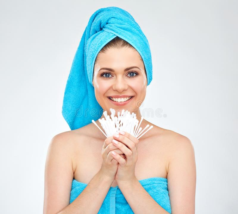 Smiling woman wearing towel holding cotton stick. Isolated portrait stock photos