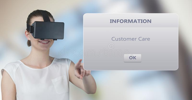 Smiling woman wearing VR glasses while touching information box. Digital composite of Smiling woman wearing VR glasses while touching information box royalty free stock photo