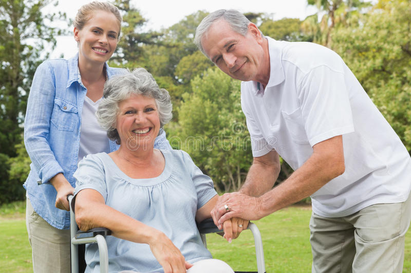 Smiling woman in wheelchair with daughter and husband royalty free stock photography