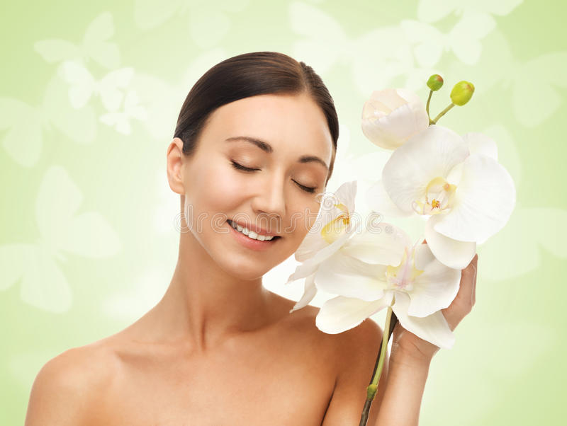 Smiling woman with white orchid flower stock photos