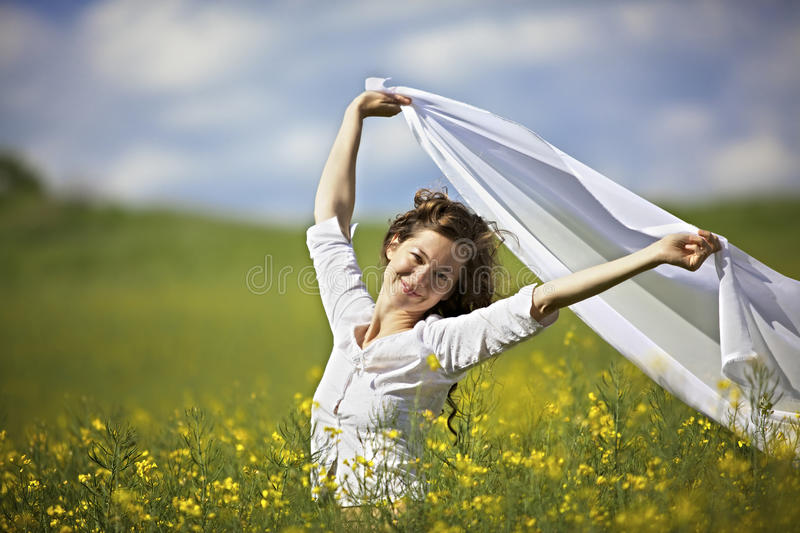Smiling woman with white piece of cloth in wind