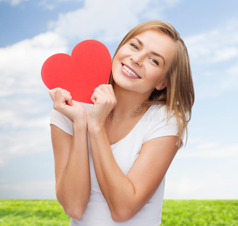 Smiling woman in white t-shirt holding red heart royalty free stock photos