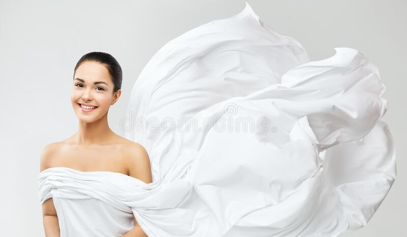 Smiling Woman in White Waving Dress, Silk Cloth Fluttering on Wind, Fashion Model Beauty Portrait royalty free stock images