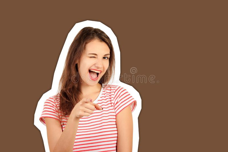 Smiling woman wink and pointing to camera. emotional girl Magazine collage style with trendy color background royalty free stock photography