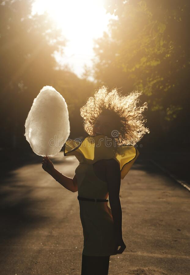 Free Smiling Woman With Curly Hair Has Fun With Cotton Candy At Sunset Stock Photo - 189399380