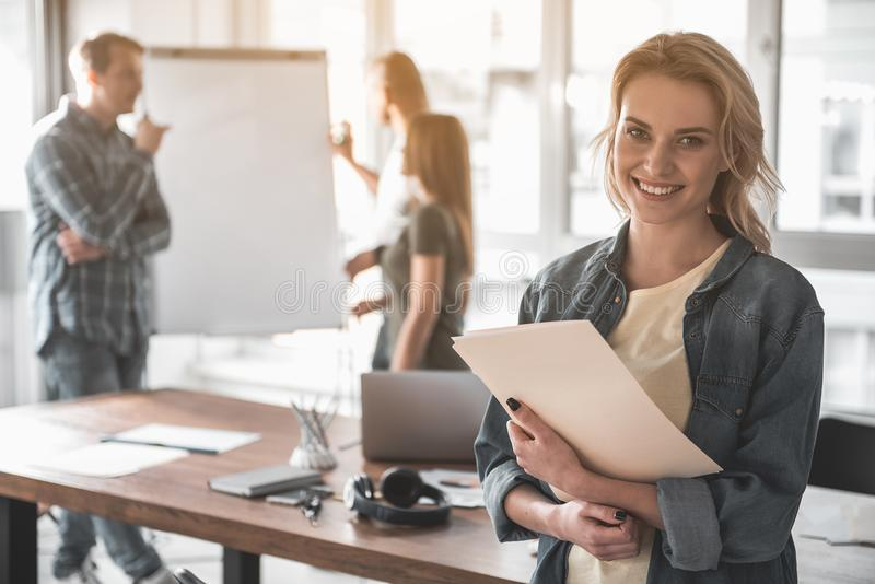 Smiling woman working with her team stock image