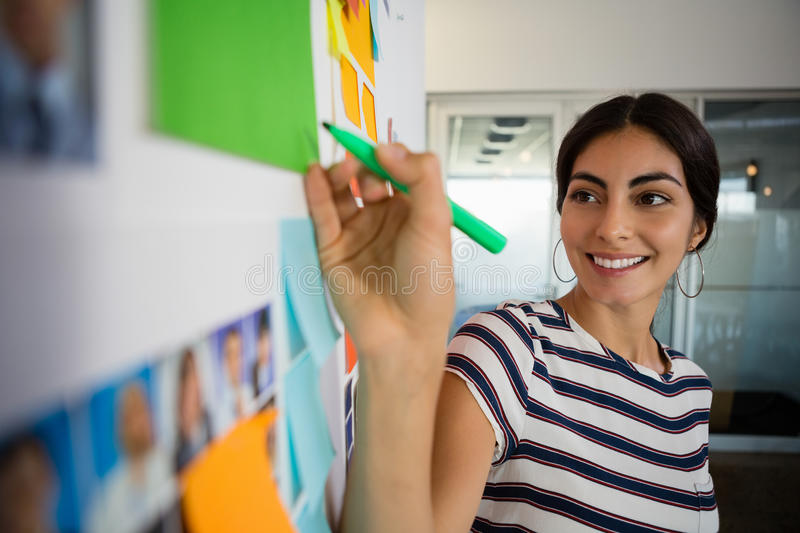 Smiling woman writing on sticky note in office stock photography