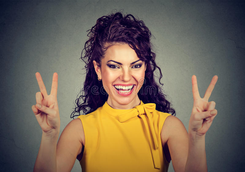 Smiling woman in yellow dress showing victory or peace sign royalty free stock image