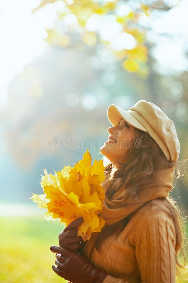 Smiling woman with yellow leaves looking up at copy space royalty free stock photo