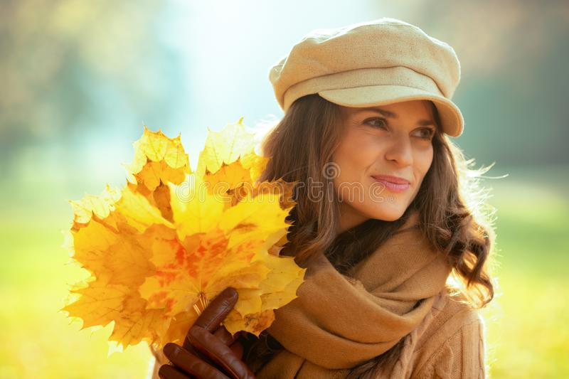 Smiling woman with yellow leaves outside in autumn park stock photography