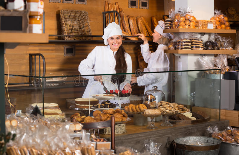 Smiling women at bakery. Two cheerful female bakers selling fresh pastry and loaves in bread section royalty free stock photography