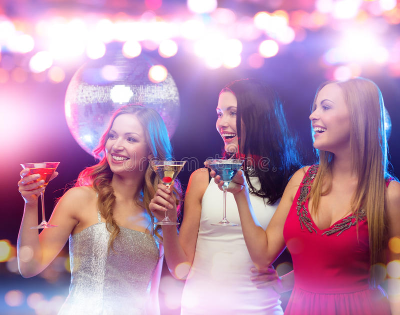 Smiling women with cocktails at night club. Holidays, nightlife, bachelorette party and people concept - smiling women with cocktails at night club royalty free stock photo