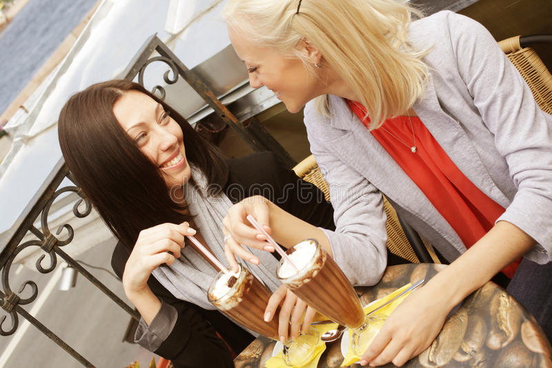 Smiling women drinking a coffee royalty free stock photography