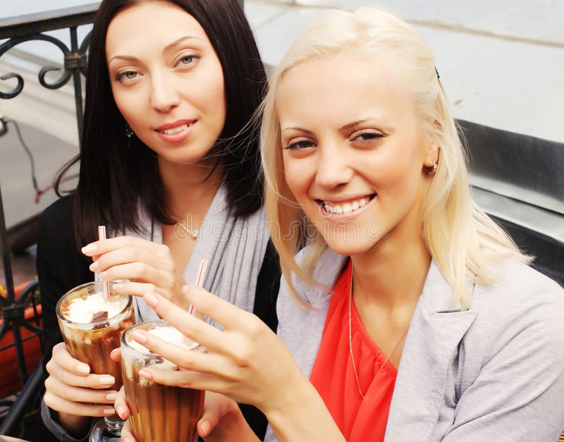 Smiling women drinking a coffee stock image