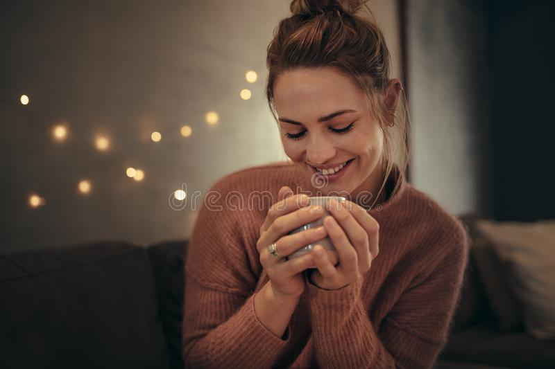 Smiling woman drinking coffee in winter at home. Smiling women drinking coffee in winter at home. Caucasian female relaxing in cozy living room and having coffee royalty free stock photo