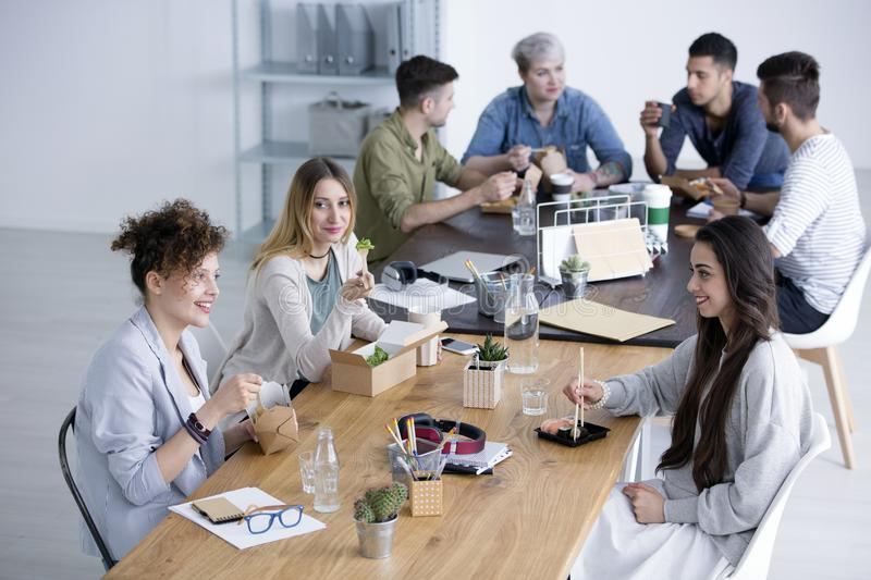 Smiling women eating lunch stock images