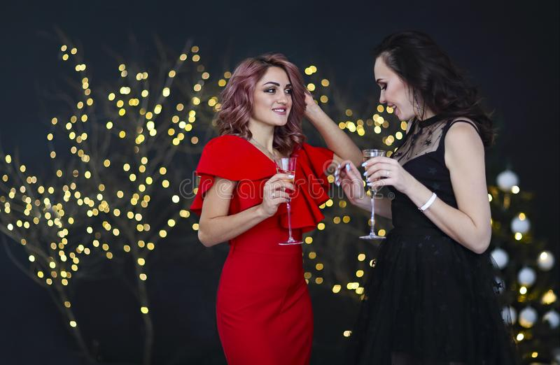 Smiling women in evening dresses with glasses of champagne over lights background. Party, drinks, holidays, luxury, friendship and celebration concept royalty free stock images