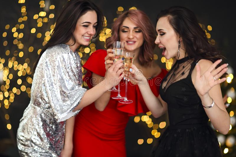 Smiling women in evening dresses with glasses of champagne over lights background. Party, drinks, holidays, luxury, friendship and celebration concept stock photo