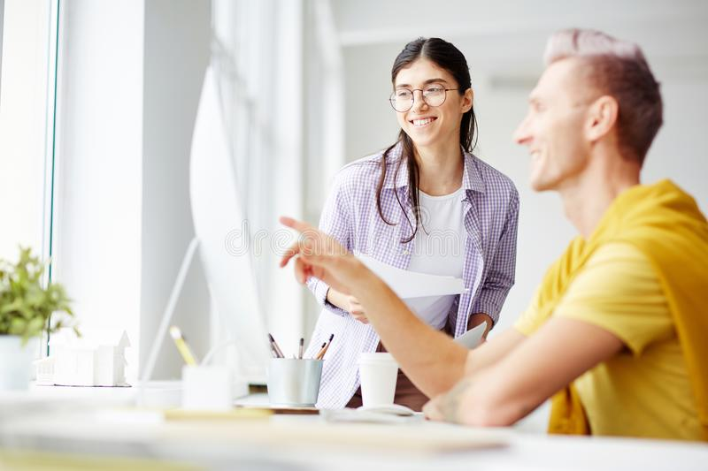 Attention to monitor. Smiling women in eyeglasses looking at monitor display while her colleague or groupmate explaining online data stock photo