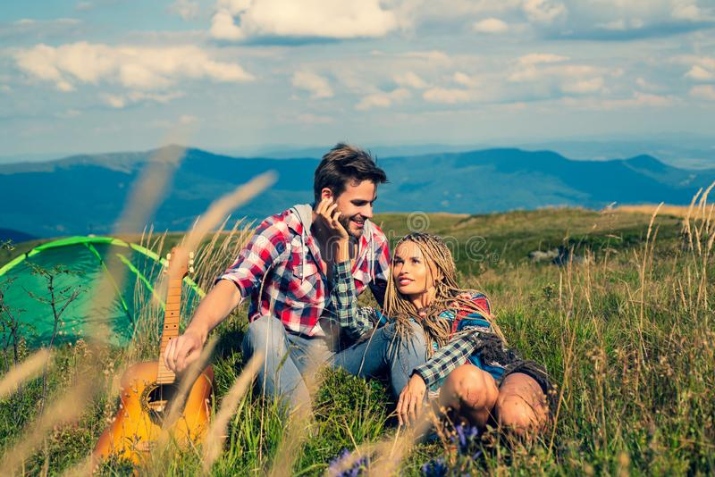 Smiling woman flirt with handsome man at the mountainside having rest at the nature. Travel couple enjoying wanderlast royalty free stock photos