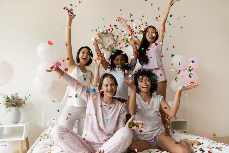 Smiling women group wear sleepwear celebrate party throw confetti up stock image
