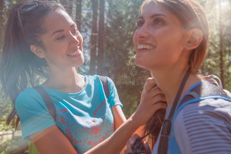 Smiling woman helping friend at hiking trail path in forest woods during sunny day.Group of friends people summer stock image