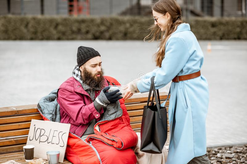 Woman giving food to a homeless beggar. Smiling women helping homeless beggar giving some food outdoors. Concept of helping poor people stock photography